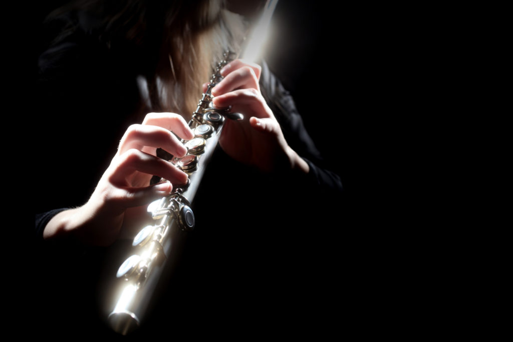 Flute playing flutist musician performer with bright musical instrument on the black background